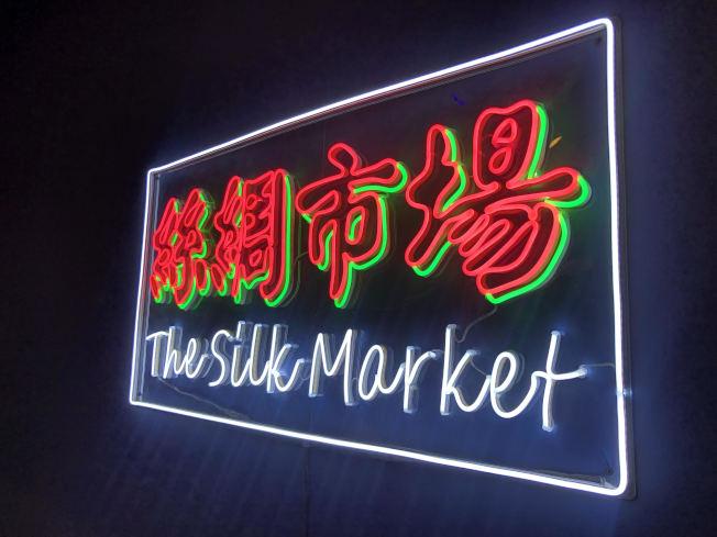 「集市」展廳的中文霓虹標識格外顯眼。(記者張晨/攝影)