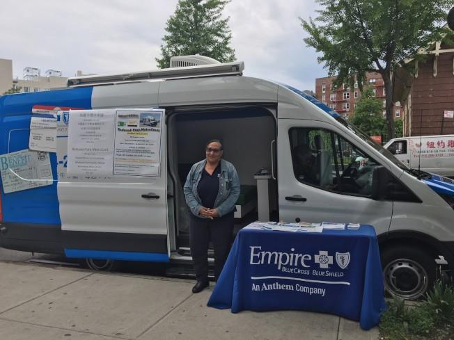 大都會運輸署工作人員Julie Perez在帝國藍十字藍盾健保公司社區服務車協助民眾辦理半價地鐵卡。