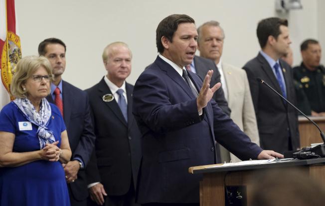 佛羅里達州長德桑提斯(發言者)14日簽署州法,禁止地方政府實行保護無證移民不被遣返的庇護政策。(美聯社)
