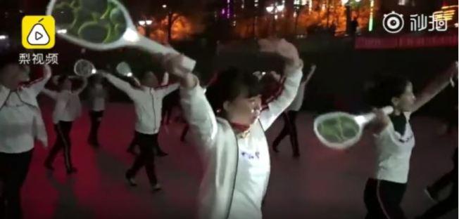 大爺大媽自帶滅蚊拍跳廣場舞。(視頻截圖)