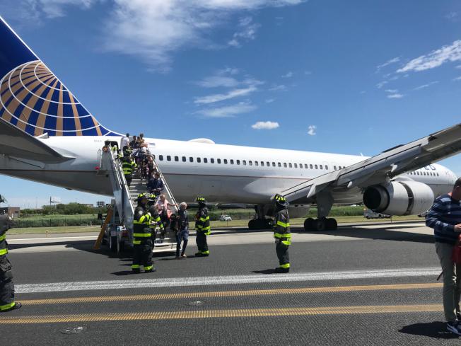 聯航班機在紐瓦克機場降落時發生意外,機場工作人員用舷梯幫助機上乘客和機組人員離開飛機。(美聯社)