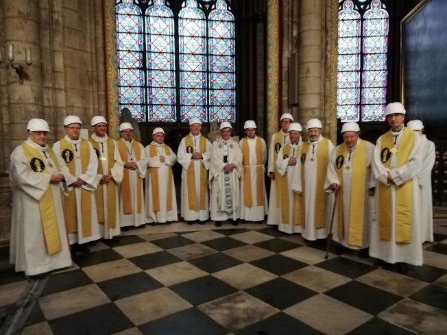 神職人員和信徒戴上安全帽,參加巴黎聖母院災後首場彌撒。(Getty Images)
