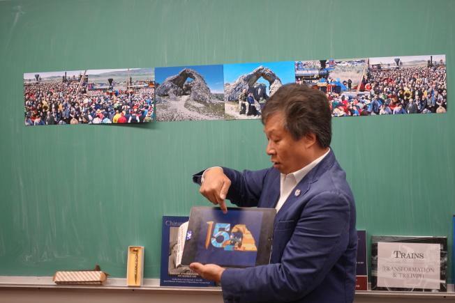 李宗保指出150周年紀念章上的數字0以華裔門形狀設計。(記者金春香/攝影)