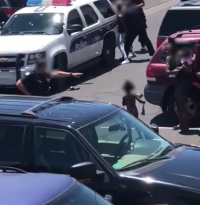 旁觀者拍攝的錄像顯示,一名警察拔槍指向母親和小孩。(KNXV截圖)