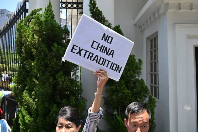 特首林鄭月娥宣布暫緩修訂「逃犯條例」時,香港政府總部外面示威者高舉反送中標語。(Getty Images)