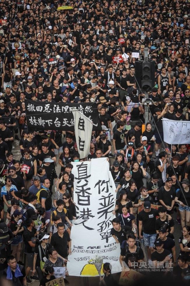 參與反送中遊行的香港民眾高舉布條表達訴求,遊行隊伍行進時高喊要求行政長官林鄭月娥下台。中央社記者