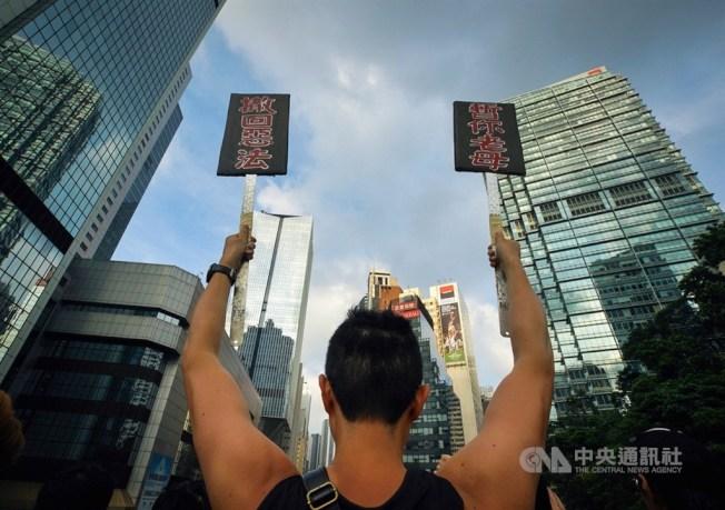 香港反送中民眾16日再度上街遊行,要求政府撤回修訂逃犯條例草案及行政長官林鄭月娥下台等,有民眾高舉自製標語表達訴求。中央社