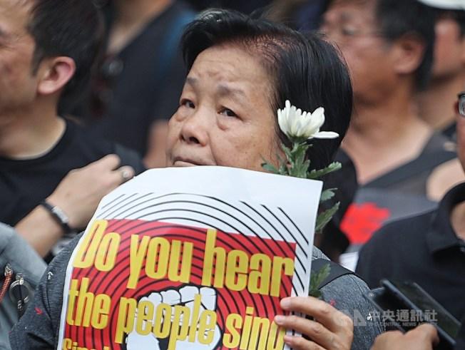 香港民眾16日參與反修訂逃犯條例大遊行,民眾手持白花,悼念墜樓身亡的反送中男子。中央社