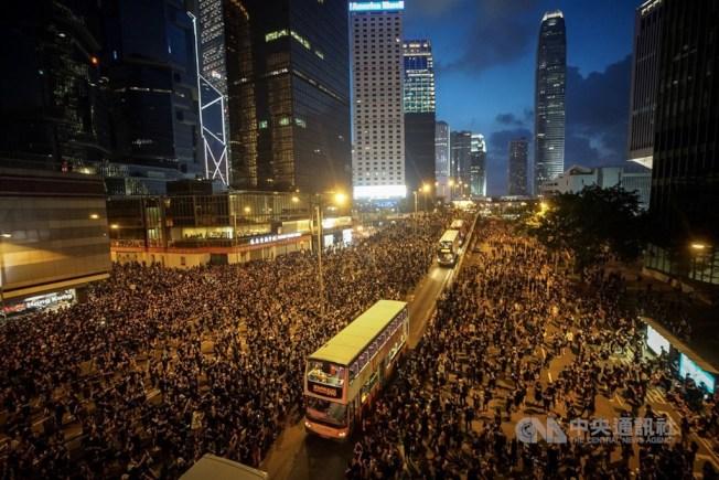 香港民眾16日身穿黑衣上街表訴求,遊行群眾移動至未封閉車道。中央社