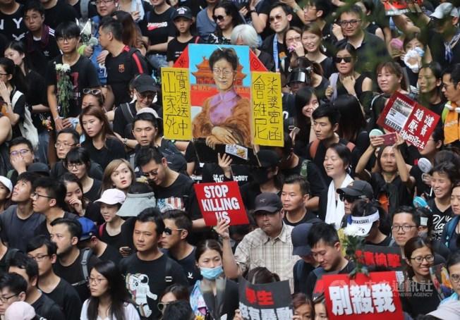 香港泛民主派團體民間人權陣線16日再次發起反修訂逃犯條例大遊行,大批民眾身穿黑衣走上街頭,有人高舉繪製的標語要求行政長官林鄭月娥下台。中央社