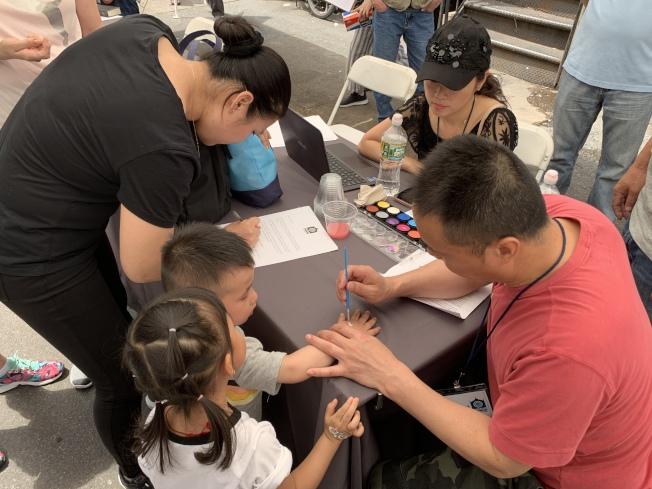 艺术家在小朋友手上演示彩绘。(记者和钊宇/摄影)