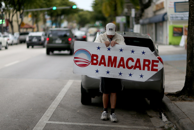 川普政府已制定法規,將放寬對不合乎歐記健保標準的短期健保計畫的限制。圖為佛州一名男子在街頭持「歐記健保」廣告牌,為一家健保業者招徠顧客。(Getty Images)