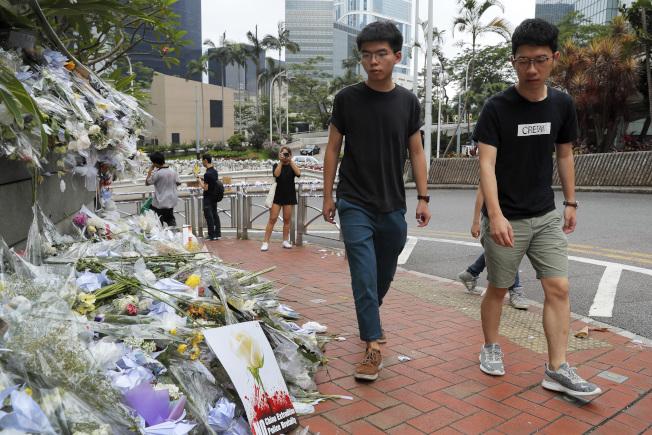 黃之鋒(左)17日出獄後與香港眾志常委羅冠聰(右)到金鐘太古廣場外,為日前反對修訂《逃犯條例》而墜樓身亡的示威者獻花悼念。(美聯社)