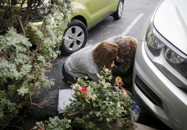 一個全副武裝的蒙面男子17日在達拉斯市中心的聯邦法院外開火後,兩名聯邦員工躲在車旁掩蔽。(美聯社)
