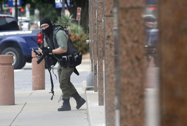 一個全副武裝的蒙面男子17日在達拉斯市中心的聯邦法院外開槍,但他還沒有對任何人造成傷害,就被趕到的警員擊斃。圖為案發時達拉斯「晨間新聞」的攝影記者在現場拍下的槍手照片。(美聯社)