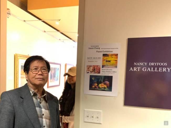 張哲雄攝於肯恩大學畫展。(主辦單位提供)