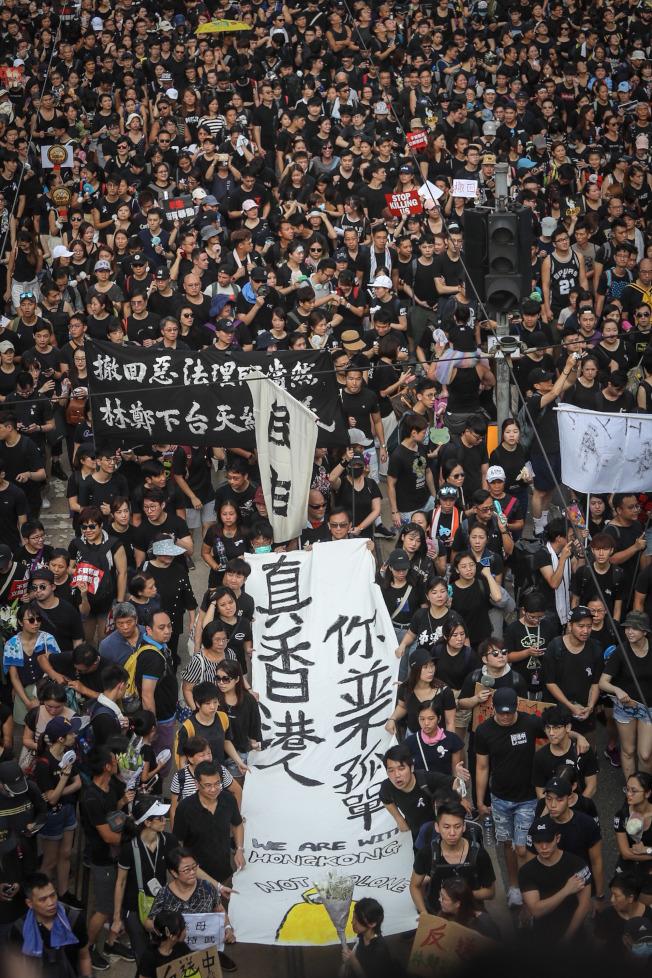 洛杉磯時報分析認為,香港已發展出一種全新的社運模式,即「沒有領袖、群眾自發參與」。圖為民陣16日再次發起大遊行,民眾身穿黑衣上街,高舉布條表達訴求。(中央社)