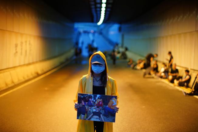 一名抗議者17日身穿黃雨衣、舉著示威者受傷的照片,要求警方撤回對六一二示威集會的「暴動」定性。(路透)