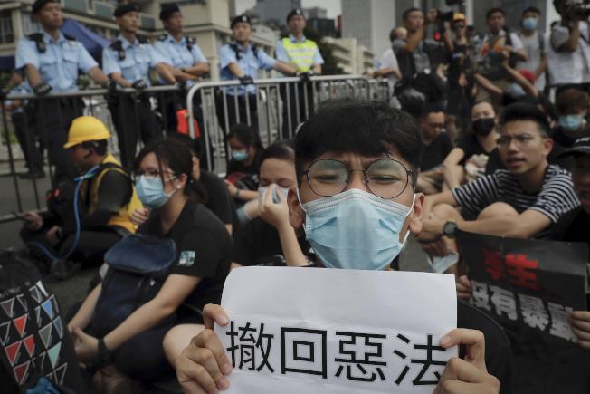 反送中抗議的港人不撤不散, 現場17日放眼望去都是戴上口罩的黑衣年輕人,要求特首下台,撤回惡法。(美聯社)