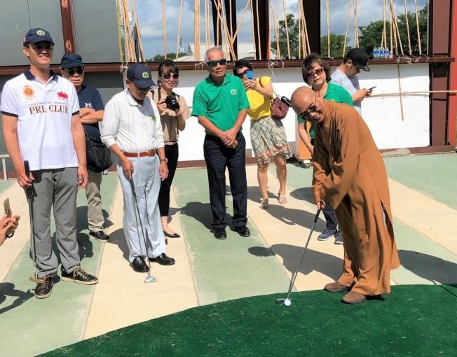 德州佛教會會長宏意法師(前)在恆豐銀行吳文龍董事長所捐建的迷你高爾夫球場上開球。(德州佛教會提供)