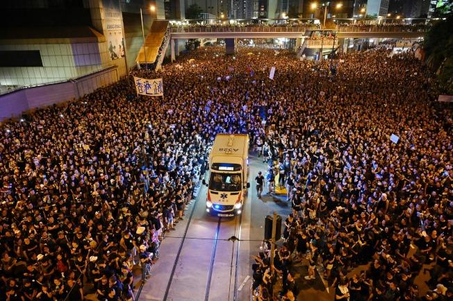 大批港人16日響應民陣號召上街遊行,33人不適送院,當救護車穿過人群救援,遊行人士立即主動「開路」。(Getty Images)