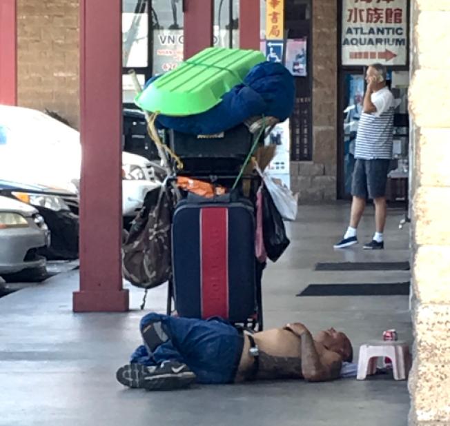 遊民半裸在餐館前睡覺。(記者陳開/攝影)