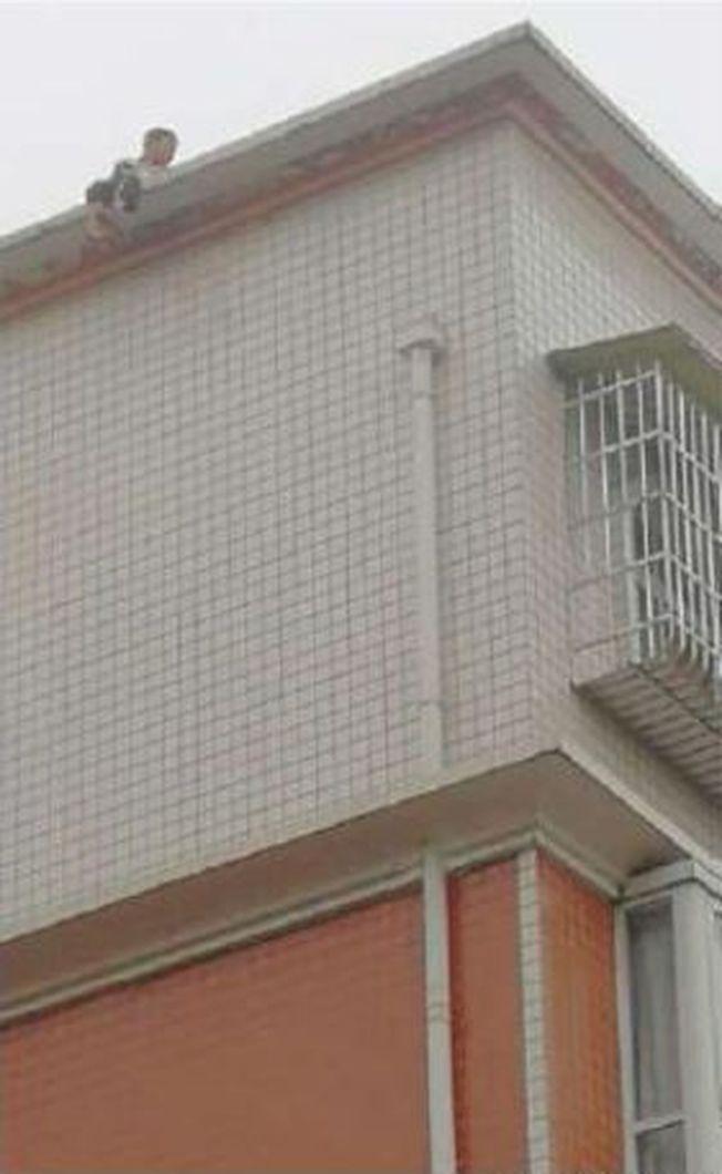 小華爬上七樓房頂,想用極端方式逼父親現身。(取材自成都商報)