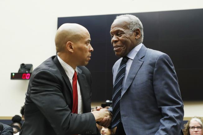 眾院司法委員會19日討論賠償黑奴後裔的問題。 圖為出席作證的男星丹尼葛洛佛(右)與參議員布克握手致意。(美聯社)