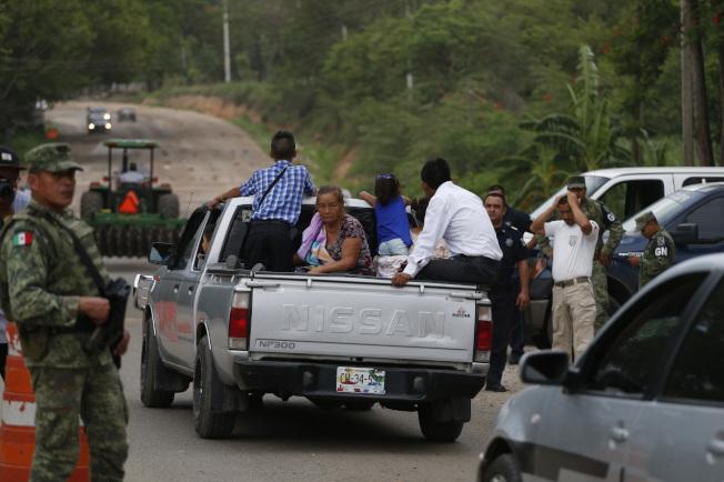 在美國壓力下,墨西哥執法單位近日加強緝拿無證移民力度。圖為墨國軍警與移民執法單位在路上檢查疑有中美洲非法移民的車輛。(美聯社)