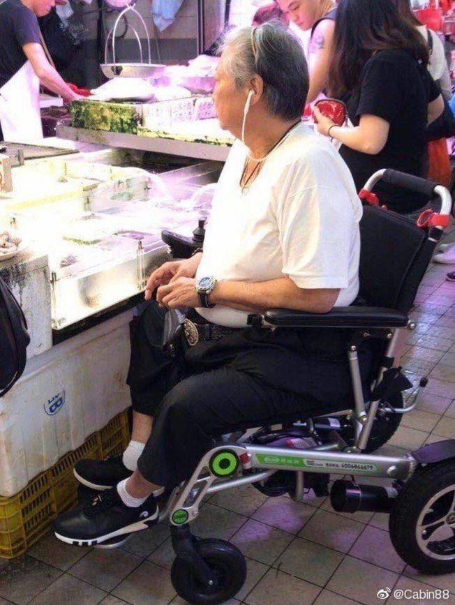 洪金寶不久前被拍到坐著輪椅陪老婆去買菜。(取材自微博)