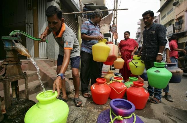 印度第六大城清奈居民正用手動幫浦裝水,後面還有人大排長龍。清奈深陷嚴重乾旱已有數周時間,傳統供水來源的4座水庫接近全面乾涸。(路透)