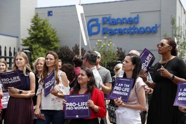 聯邦上訴法院20日裁定,川普政府向尋求墮胎的婦女實施的額外規定,在司法部上訴期間如常生效。圖為反對墮胎者在計畫生育診所前舉牌抗議。(美聯社)