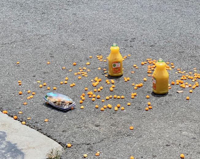 截至22日中午12時,仍有果汁、水果等被棄置路面。(記者陳開/攝影)