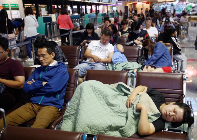 长荣空服员罢工23日进入第四天,预计将取消113个航班,由于办理签转业务须领号码牌,22日许多旅客到现场,累到睡在长椅上。(记者郑超文/摄影)