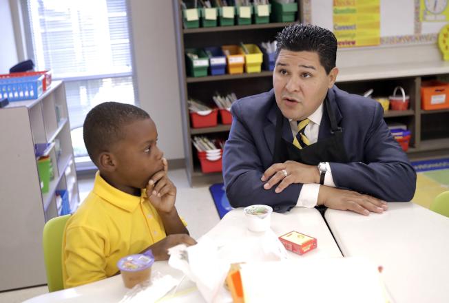 紐約市教育總監卡蘭扎陪伴一名非裔兒童念書。(美聯社)