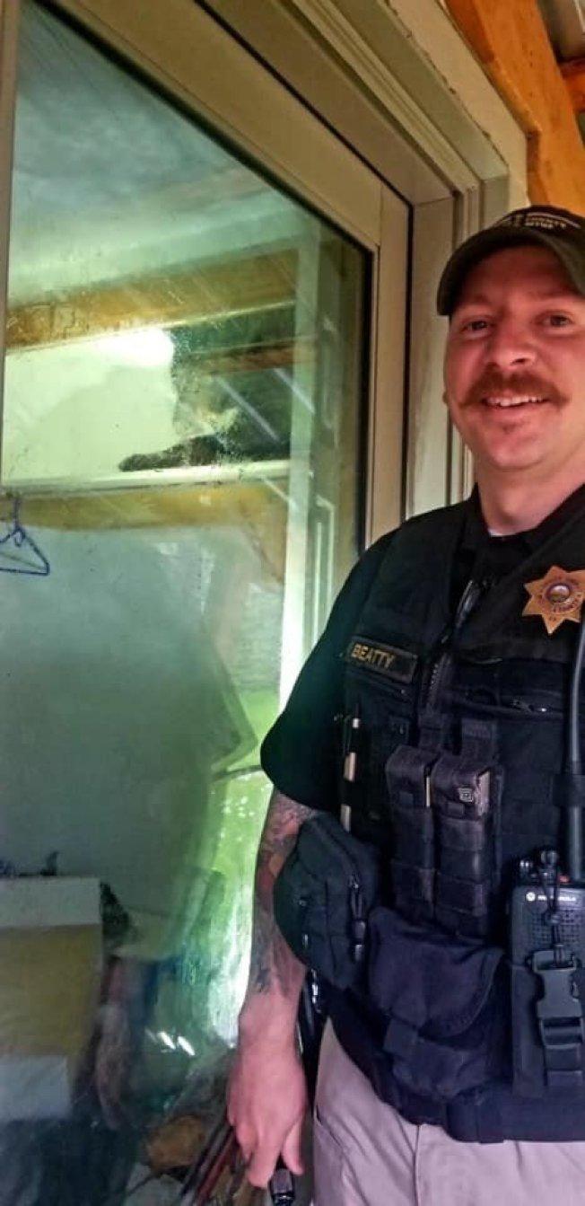 蒙大拿州一隻野生黑熊擅闖民宅,爬上衣櫃層架睡午覺,警方到場敲窗也不理。Facebook/Missoula County Sheriff's Office