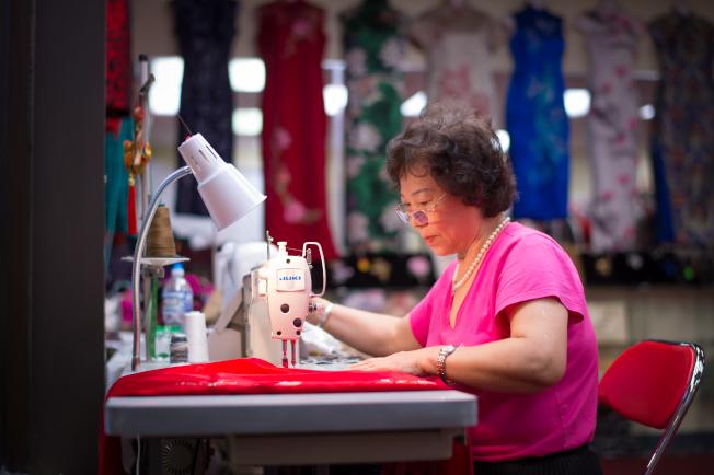 馬麗榮專心縫製衣服,後方架上旗袍均為她的作品。(馬姐提供)