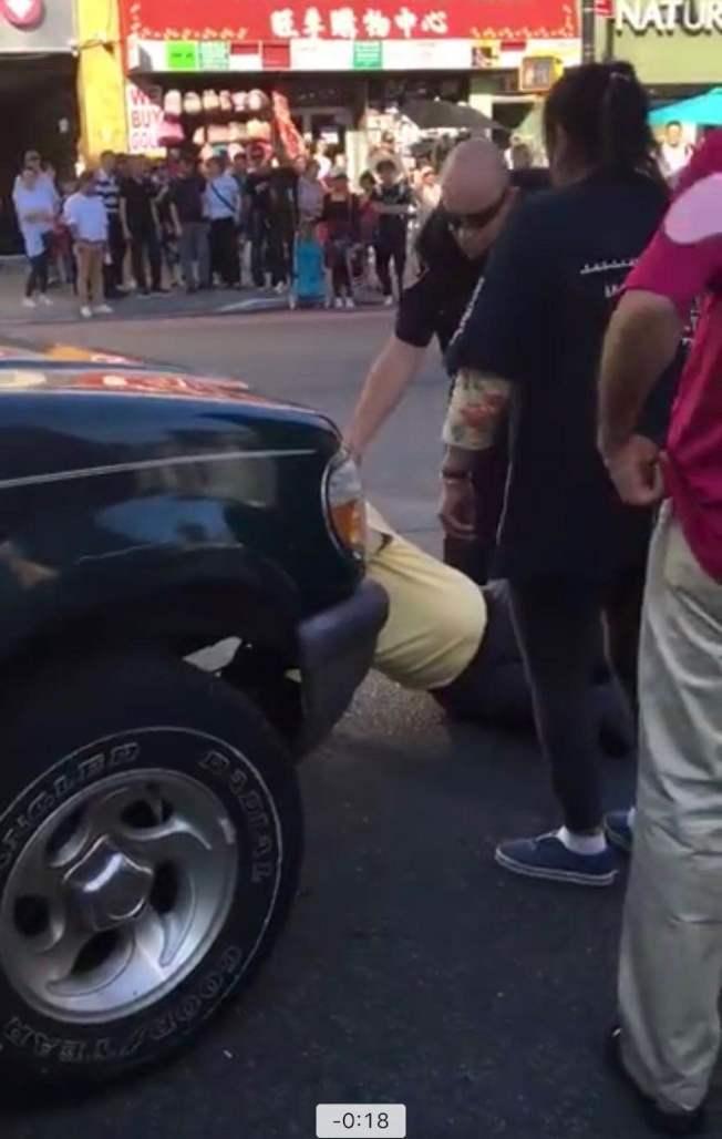 法拉盛市中心日前發生疑似碰瓷事件,路人圍觀。(視頻截圖)