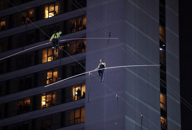 知名高空特技團體「飛翔瓦倫達家族」23日晚間在紐約時報廣場表演高空雙人對走鋼索。(美聯社)