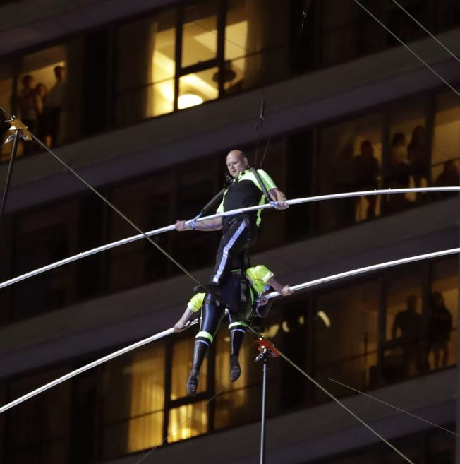 知名高空特技團體「飛翔瓦倫達家族」23日晚間在紐約時報廣場表演高空雙人對走鋼索。圖為兩人在高空中交會。(美聯社)