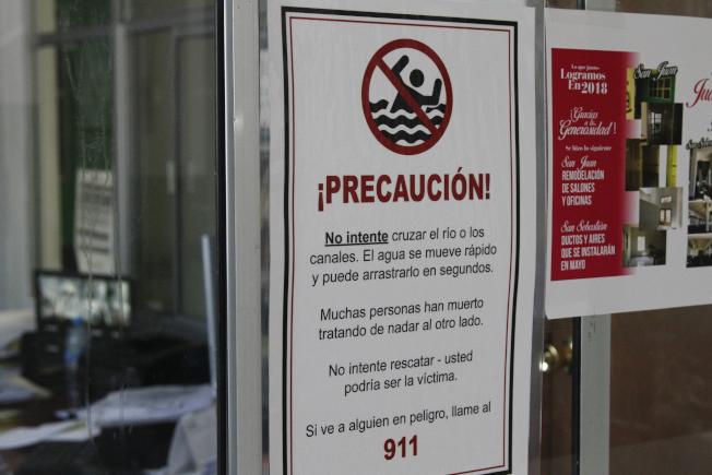在墨西哥境內靠德州艾爾帕索的華雷斯城一間教堂,貼出告示警告中美洲偷渡客在過河前往德州時注意河水漩渦。(美聯社)