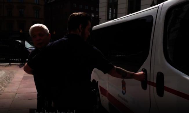 戴著手銬的喬建軍19日在瑞典法院出庭後被押上囚車,還回頭對人喊話。(取自瑞典SVT視頻)