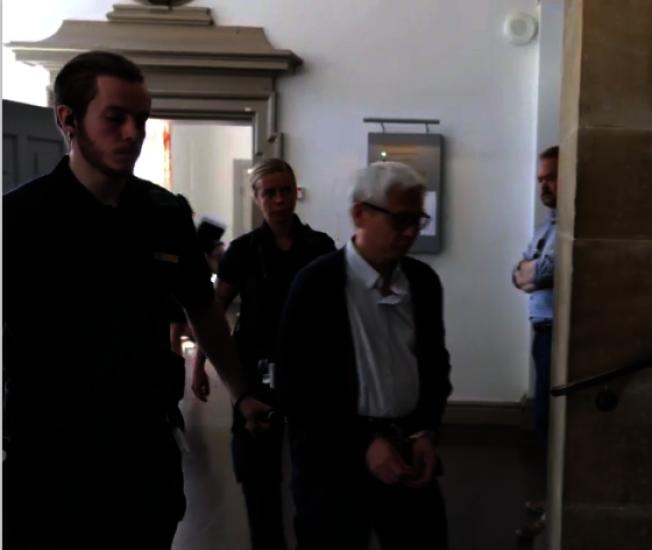 戴著手銬的喬建軍19日在瑞典法院出庭。(取自瑞典SVT視頻)