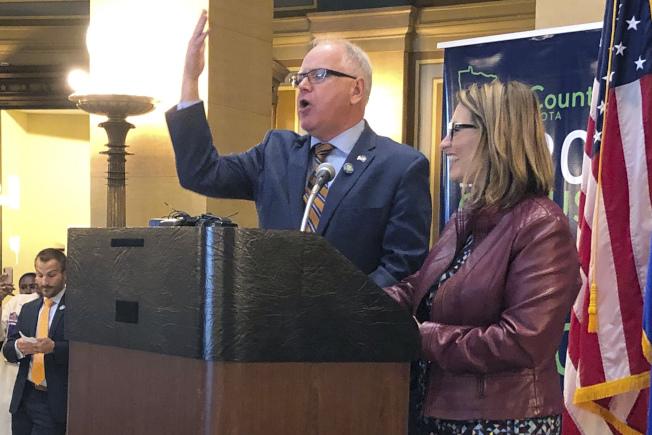 明尼蘇達州民主黨籍州長沃茲(舉手者)簽署法案後, 明州開放非法移民以領事文件在該州登記車輛。(美聯社)