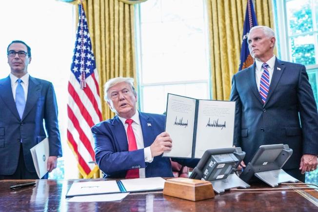 川普總統24日在白宮簽署命令,針對伊朗最高領袖哈米尼等高階官員及核心高級官員的進一步制裁金融資產。副總統潘斯(右)與財政部長米努勤(左)出席。(美聯社)