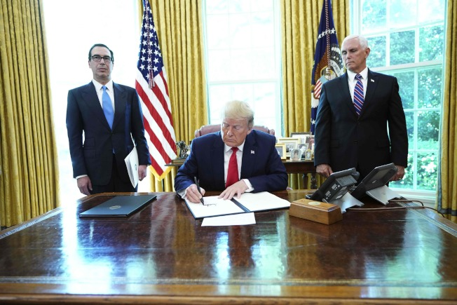 川普總統24日在白宮簽署命令,針對伊朗最高領袖哈米尼等高階官員及核心高級官員的進一步制裁金融資產,報復伊朗上周擊落美軍無人偵測機。副總統潘斯(右)與財政部長米努勤(左)出席。(美聯社)