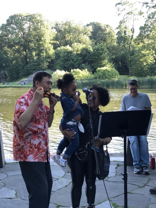 中央公園口琴匯演,何家義帶領大家演奏。(記者金春香/攝影)