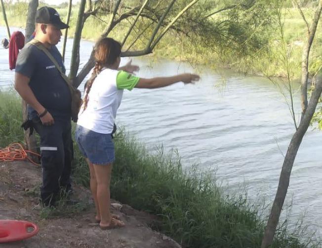 年輕的薩爾瓦多母親 Tania Vanessa Avalos(右)25日在河邊向墨國邊境官員講述渡河經過。(美聯社)