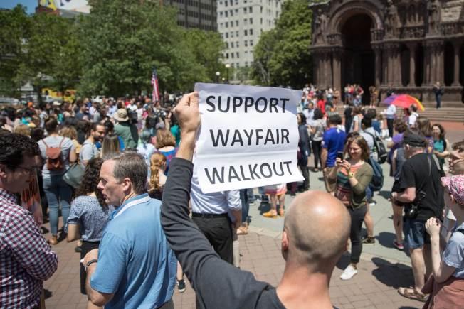 美國麻州的Wayfair員工26日罷工,舉牌抗議公司販賣睡房用品給德州的非法移民拘留中心,藉機大發移民財。(Getty Images)