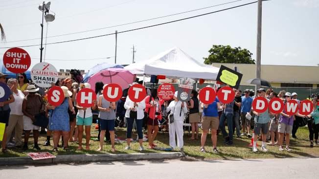 維權人士26日在佛州Homestead的一處非法移民拘留中心前抗議對待被拘移民不人道的措施,要求關閉中心。(Getty Images)